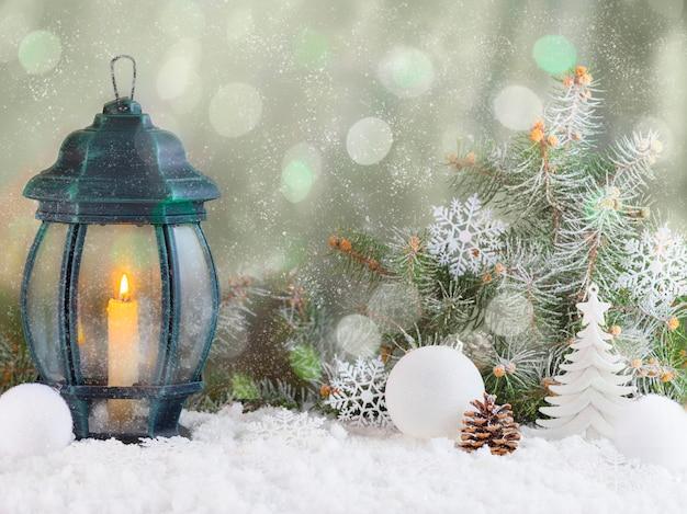 Lampion świąteczny w śniegu z gałęzi jodłowych wesołych świąt. streszczenie