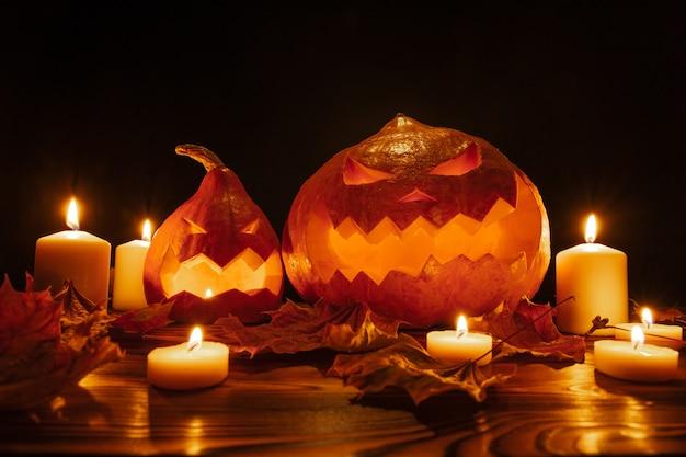 Lampiony dyniowe na czarnym tle na halloween z rzeźbionymi przerażającymi twarzami ze świecami