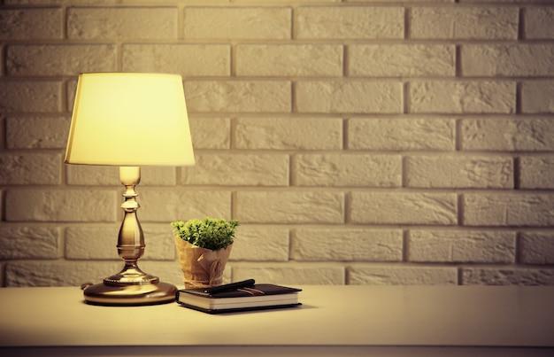 Lampka nocna na szafce na białym tle ściany z cegły