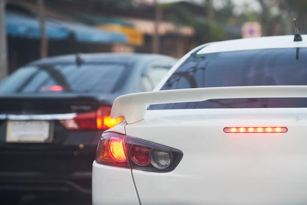 Lampka tylnego lub tylnego światła w pracy świeci na czerwono na znak stopu lub hamulca lub znak na ulicy