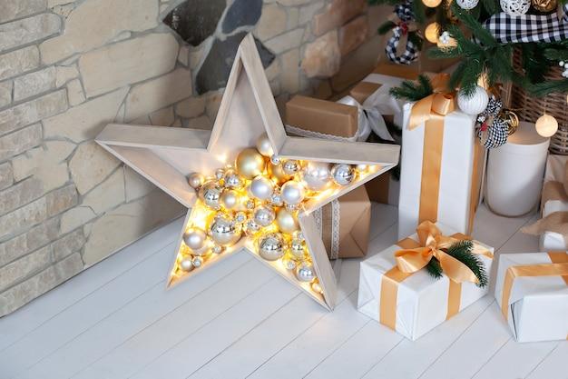 Lampki choinkowe i drewniana gwiazda ze złotymi dekoracjami świątecznymi. duża drewniana gwiazda z wieloma światłami błyszczy. ciepłe gwiazdy, lekkie girlandy, dekoracje świąteczne. ozdobna gwiazda z prezentami.