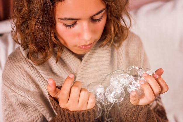 Lampki świąteczne w dłoniach. ładna młoda dziewczyna trzyma w ręku świecącą girlandę.