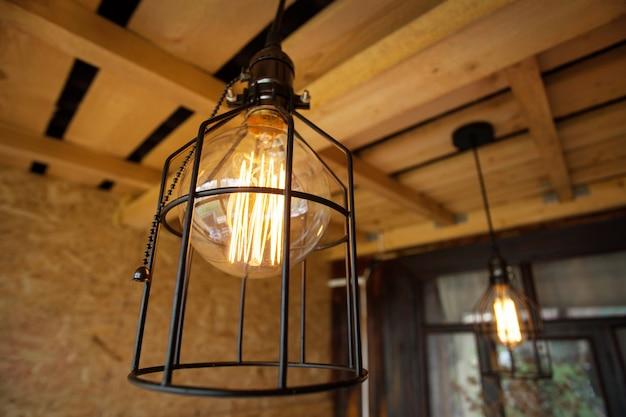 Lampy edisona w metalowym kloszu na otwartej werandzie.