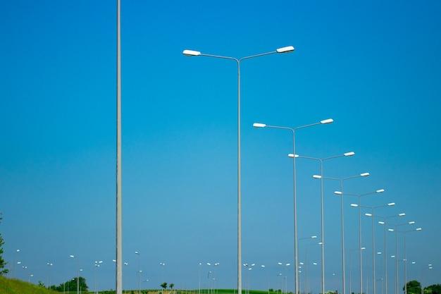 Lampy uliczne na białym tle z błękitnego nieba.