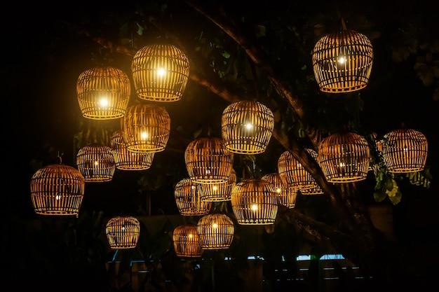 Lampy wykonane z klatki dla ptaków na ciemnym suficie, lampiony wykonane z bambusowego splotu.
