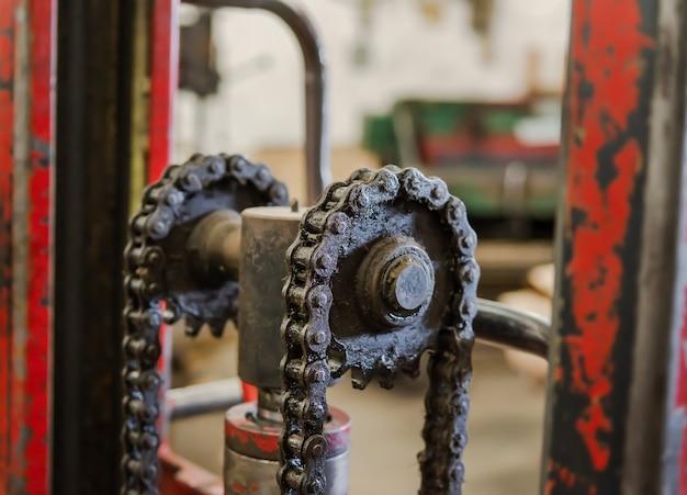 Łańcuchy mechaniczne do obróbki metali w tokarniach, które są zanieczyszczone długotrwałym olejem silnikowym i cząstkami pyłu. plamy brudnego oleju i smaru na mechanicznym łańcuchu tokarki w fabryce.