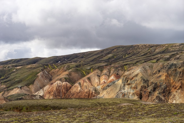 Landmannalaugar kolorowe góry na szlaku turystycznym laugavegur. islandia. połączenie warstw różnokolorowych skał, minerałów, trawy i mchu.