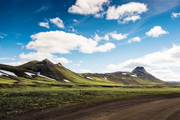 Landmannalaugar w islandii. zielona góra i jasny niebieskiego nieba tło z czarnym gr