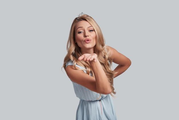 Łapać! atrakcyjna młoda kobieta dmucha buziaka i patrzy na kamerę, stojąc na szarym tle