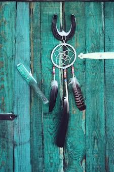 Łapacz snów i podkowa na tle stare drewniane drzwi. domowy wystrój z koralikami i piórami.