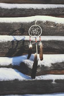 Łapacz snów na stare drewniane ściany pokryte śniegiem tło. domowy wystrój z koralikami i piórami.