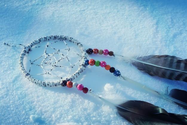Łapacz snów na tle śniegu. ręcznie wykonany wystrój z piórami i kolorowymi koralikami.