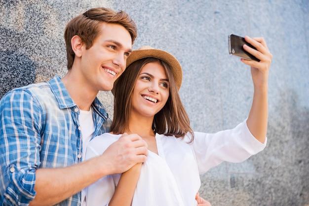 Łapanie jasnych chwil życia. piękna młoda kochająca para robi selfie za pomocą smartfona i uśmiecha się, opierając się o ścianę