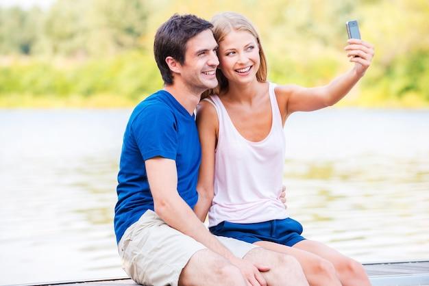 Łapie wspaniałe chwile życia. piękna młoda kochająca para siedzi na nabrzeżu i robi selfie za pomocą smartfona
