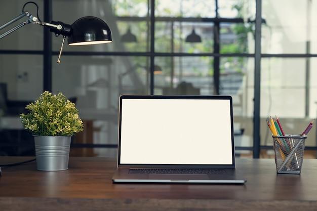 Laptop biały ekran i lampy z papeterią na stole.