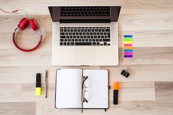Laptop blisko eyeglasses, notepad i hełmofonów na podłoga