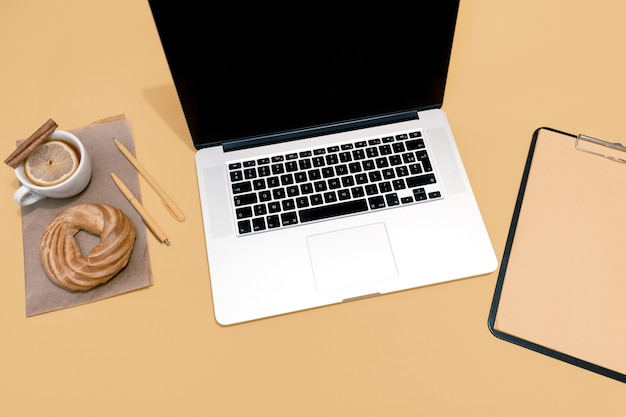 Laptop, ciasto, filiżanka herbaty lub grzane wino i wznowienie arkusza na pastelowo pomarańczowym stole
