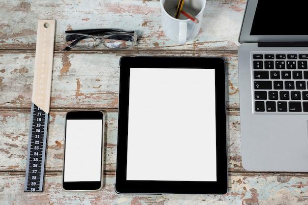 Laptop, cyfrowy tablet, smartfon, okulary i linijka