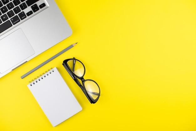 Laptop, czarne okulary, ołówek, terminarz notatnika na żółtym tle. leżał na płasko. skopiuj miejsce.