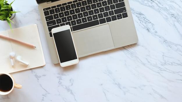 Laptop, czarny pusty ekran smartfona, bezprzewodowe słuchawki, ołówek, notatki i roślina doniczkowa stawiająca na marmurowym stole.