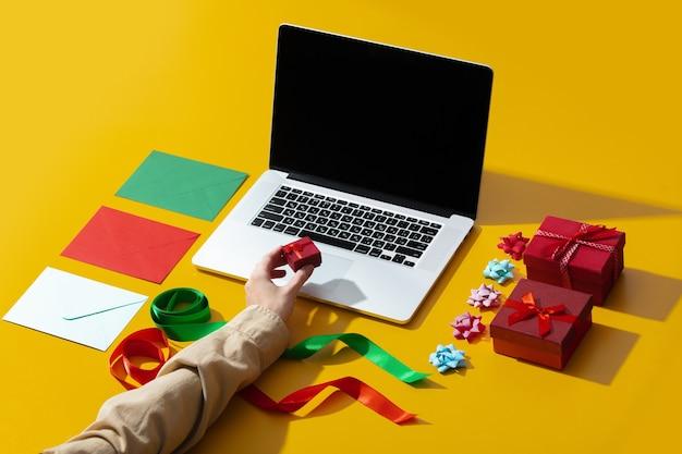 Laptop, dłoń trzymająca prezent i różne rzeczy do pakowania prezentów