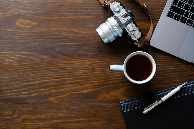 Laptop, filiżanka herbaty, aparat fotograficzny i notatnik leżą na ciemnym drewnianym stole. miejsce pracy fotografa lub freelancera.