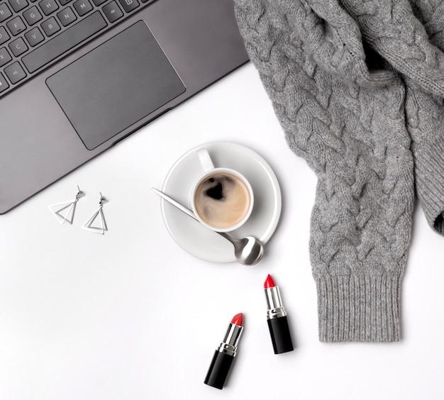 Laptop, filiżanka kawy, sweter, pomadki i okulary. stylowe biurko.