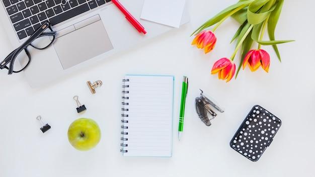 Laptop i artykuły papiernicze w pobliżu kwiatów tulipanów i jabłka