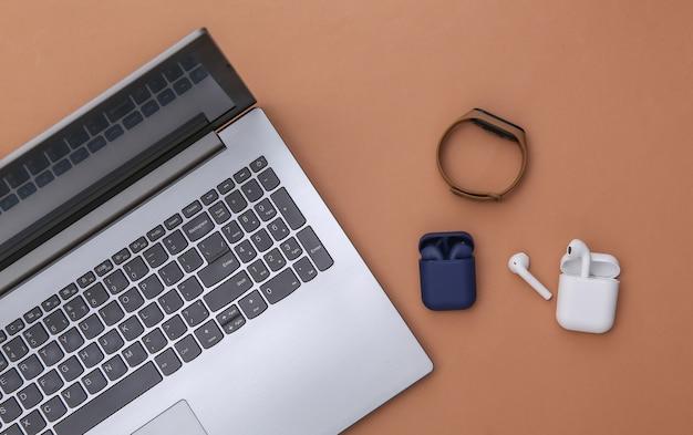 Laptop i bezprzewodowe słuchawki z etui z ładowarką i inteligentną bransoletką na brązowym tle. widok z góry