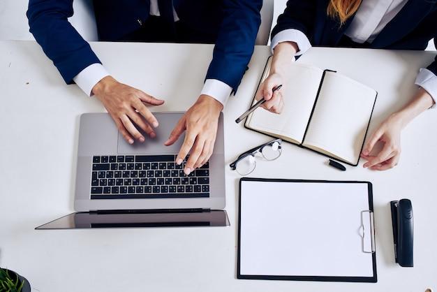 Laptop i dokumenty kolegów na stole widok z góry