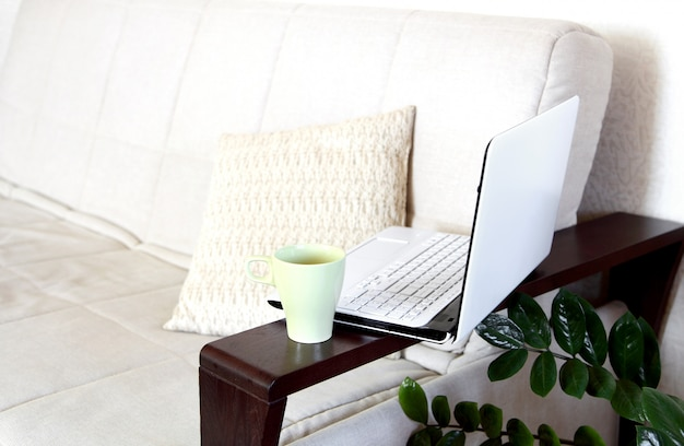 Laptop i filiżanka herbaty na kanapie. domowe biuro.
