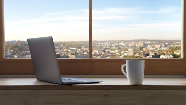 Laptop i filiżanka kawy na drewnianym parapecie z widokiem na miasto