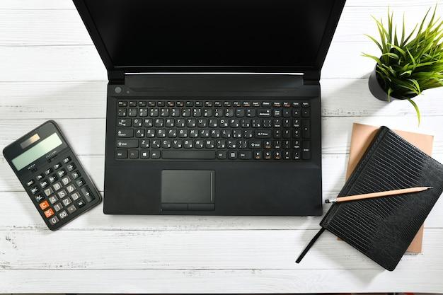 Laptop i kalkulator na drewnianym stole
