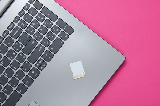 Laptop i karta pamięci sd na różowym papierze o geometrycznych kształtach