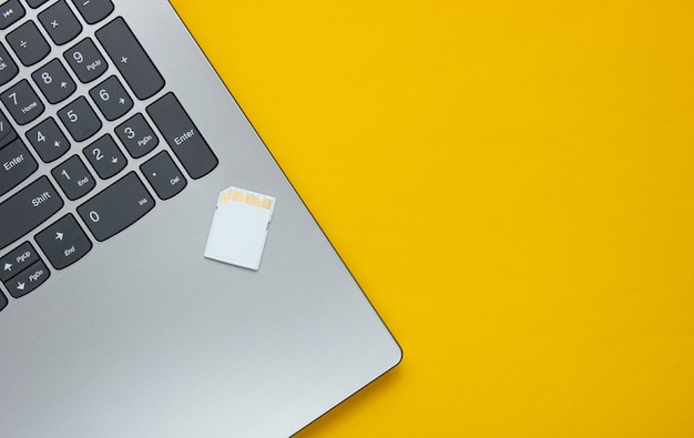 Laptop i karta pamięci sd na żółtym papierze o geometrycznych kształtach