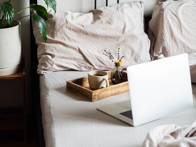 Laptop i kawa na łóżku w sypialni