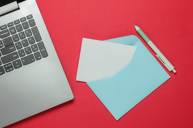 Laptop i koperta z listem na czerwonym tle. walentynki. widok z góry
