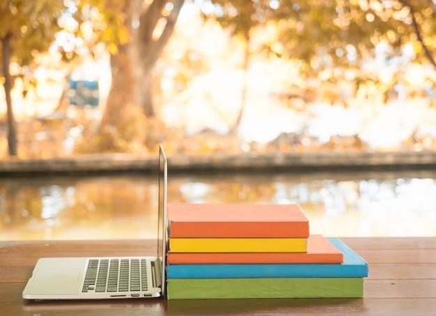 Laptop i książki na stole dla edukacji.