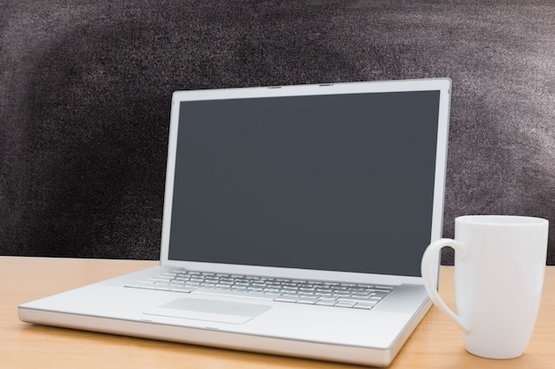 Laptop i kubek z tablicy