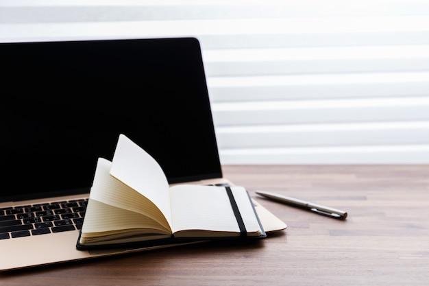 Laptop i notatnik na drewnianym stole