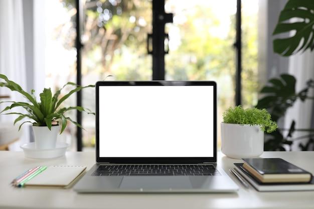 Laptop i notebooki z doniczkami na białym stole do pracy w domu