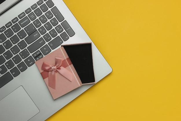 Laptop i otwarte pudełko z kokardą na żółtym tle. kompozycja na boże narodzenie, urodziny lub wesele. widok z góry