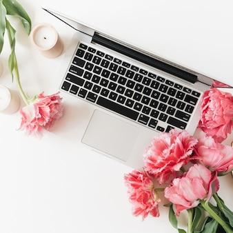 Laptop i piękne różowe piwonie tulipanów kwiaty na białym tle