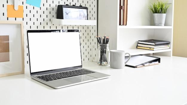 Laptop i półki z artykułami biurowymi