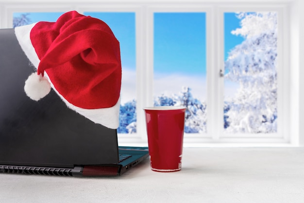 Laptop i prezenty na stole z święty mikołaj kapeluszem w domu z panoramicznym widokiem