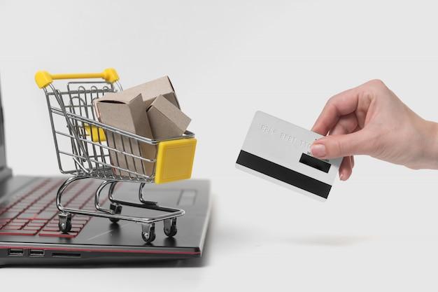 Laptop i ręka trzyma kartę kredytową