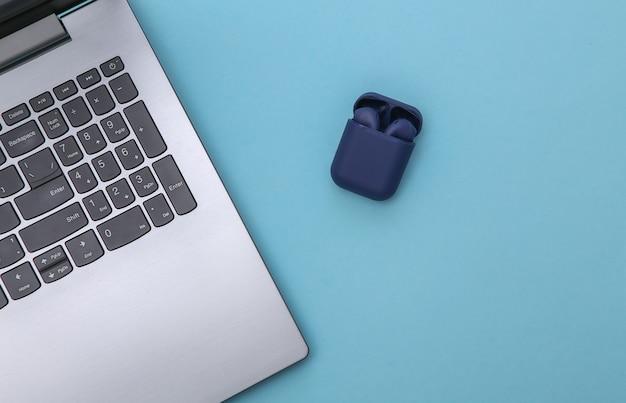 Laptop i słuchawki bezprzewodowe z etui na ładowarkę na niebieskim tle. widok z góry