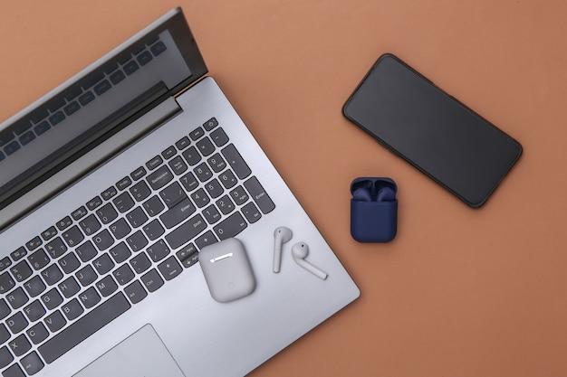 Laptop i słuchawki bezprzewodowe z etui z ładowarką i smartfonem na brązowym tle. widok z góry