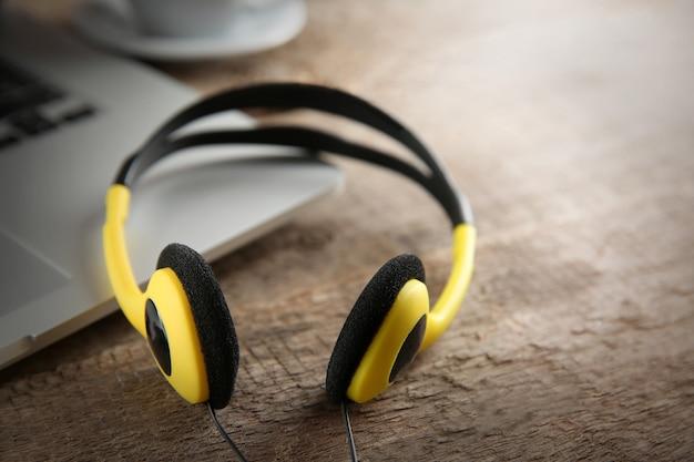 Laptop i słuchawki na drewnie