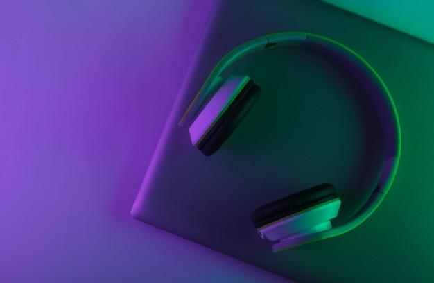 Laptop i słuchawki z neonowo zielonym i fioletowym światłem